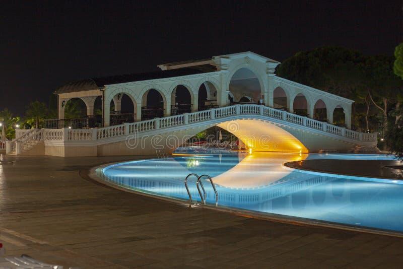Bro över simbassäng i hotell med nattbelysning arkivfoton