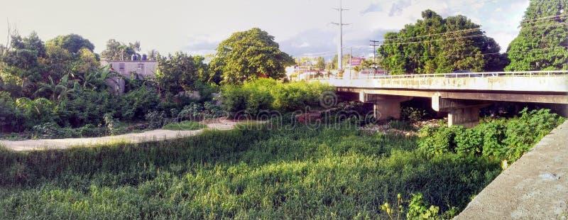 Bro över strömmen som är kontaminerad med avskräde royaltyfria foton