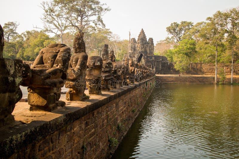 Bro över vallgraven på den södra porten av Angkor Thom royaltyfria bilder
