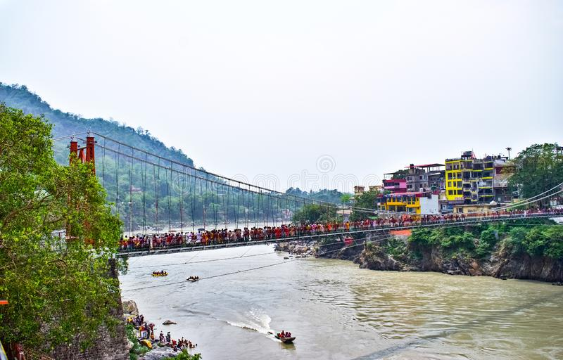Bro för Lakshman jhulaupphängning i Rishikesh med fartyg, i den haridwar gangafloden och rafting arkivfoton