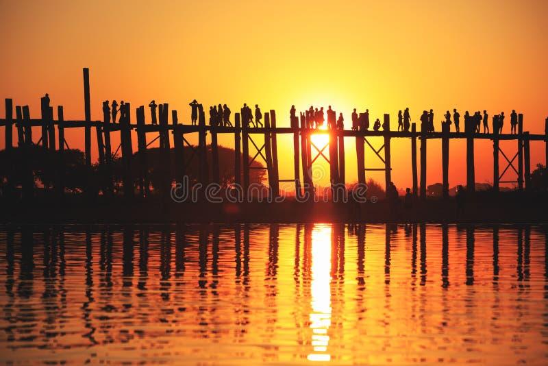 Bro för U Bein på solnedgången med folk som korsar Ayeyarwady flod, M arkivfoto