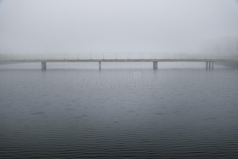 Bro i lugna fridsamt dimmigt väder i det vita drömlika landskapet royaltyfri fotografi