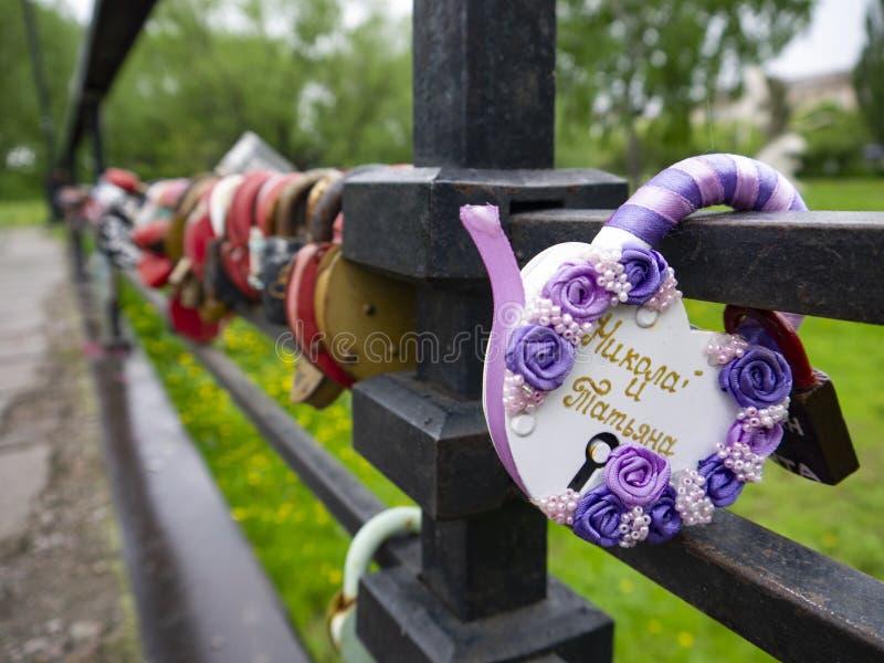 Bro med många lås med namnen av nygifta personerna som ett tecken av förälskelse Hårda hänglås med tangenter som kastas in i flod arkivbilder