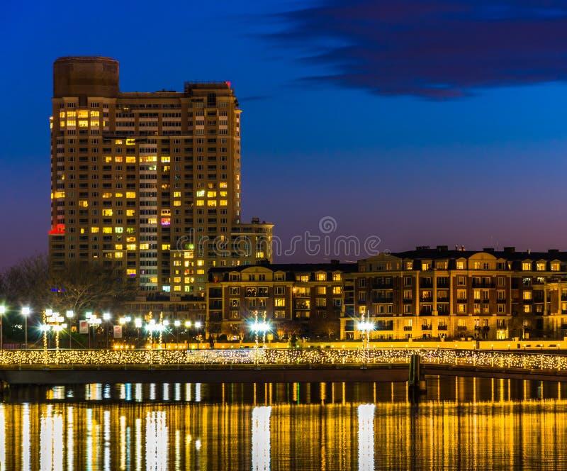 Bro och byggnader på natten, på den inre hamnen av Baltimore, royaltyfria foton