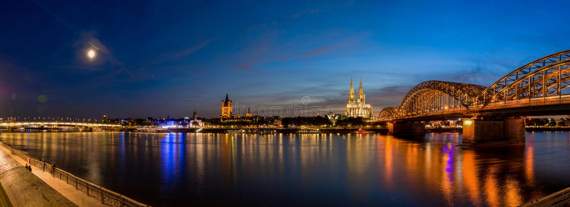 Bro och domkyrka av Cologne, Tyskland efter solnedgång i blå timmepanorama royaltyfri bild
