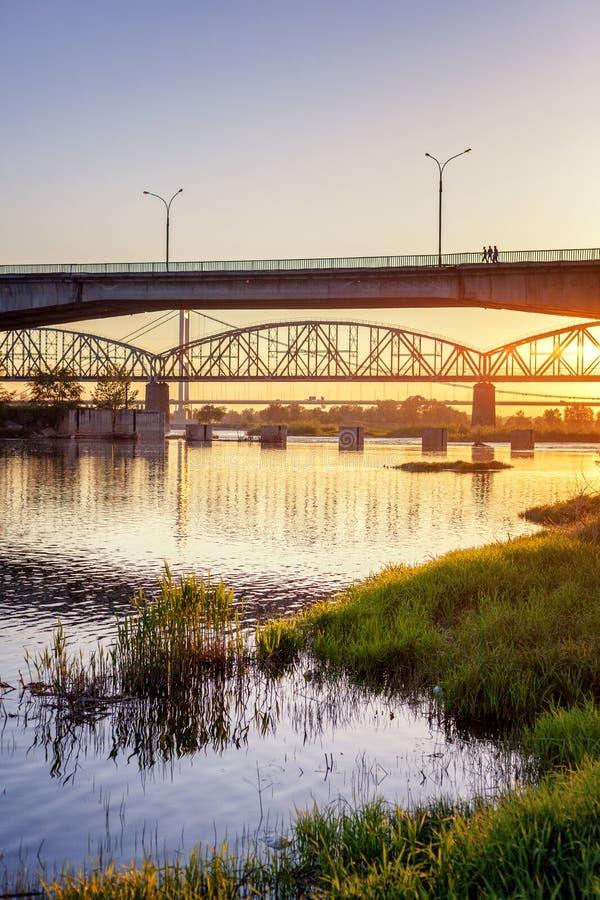 Bro och flod i strålarna av inställningssolen, härlig stad royaltyfri foto