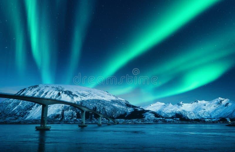 Bro och norrsken ?ver sn?ig berg p? natten arkivbild