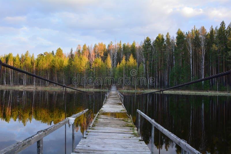 Bro på vattnet Aftonsol royaltyfria bilder