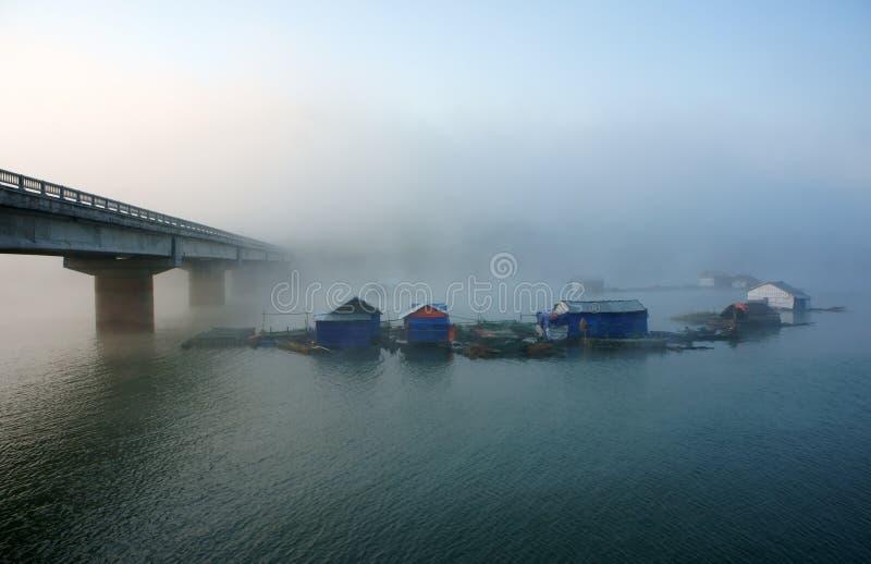 Bro som fiskar lilla byn på sjön i dimma royaltyfria bilder
