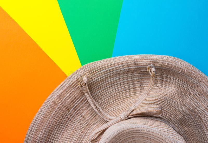 Broad brimmed women`s straw hat on rainbow multicolored pinwheel striped sunburst background. Summer vacation fashion stock image
