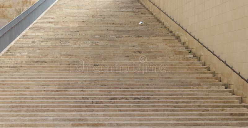 Broad stairway made from beige rock stock photography