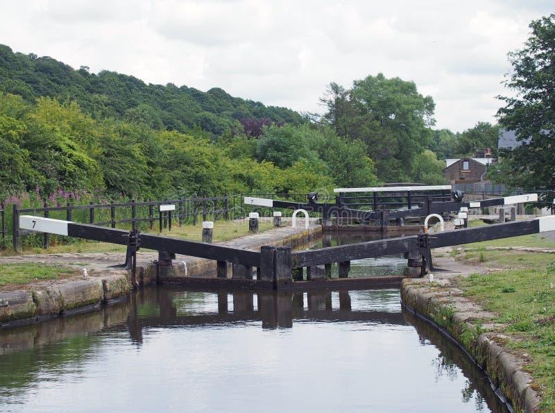 Broadbottom lås på rochdalekanalen på den västra utkanten av mytholmroyd - yorkshire med sommarträd som fodrar dalen royaltyfri fotografi