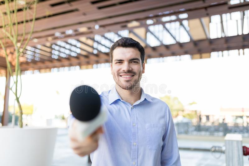 Broadcaster Holding Mic For Interview. Good looking TV reporter with microphone conducting interview and asking for questions stock images