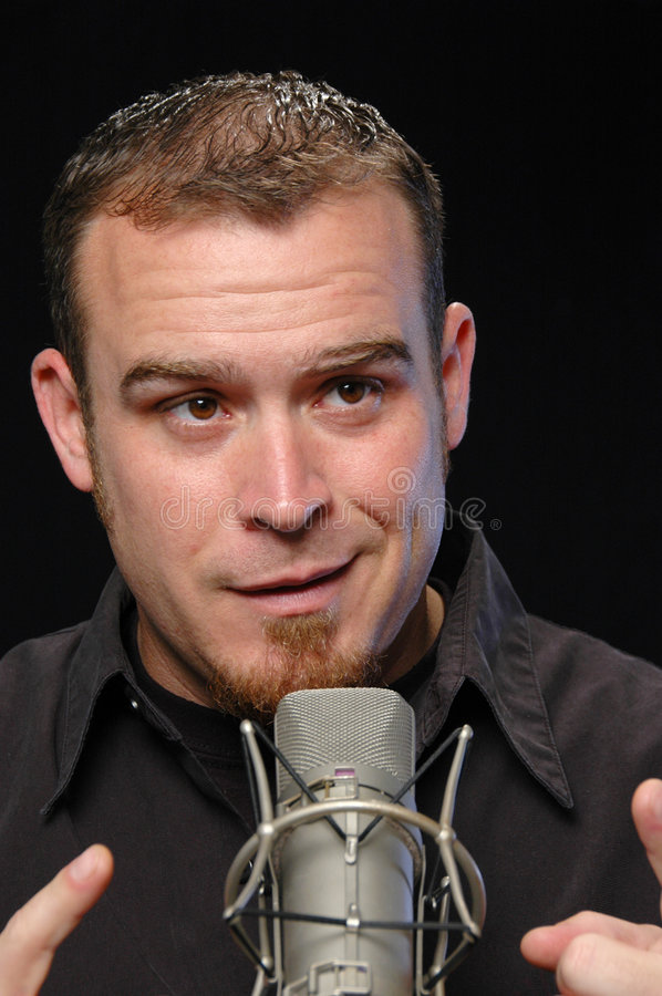 Broadcaster on the microphone. On a black background stock photography