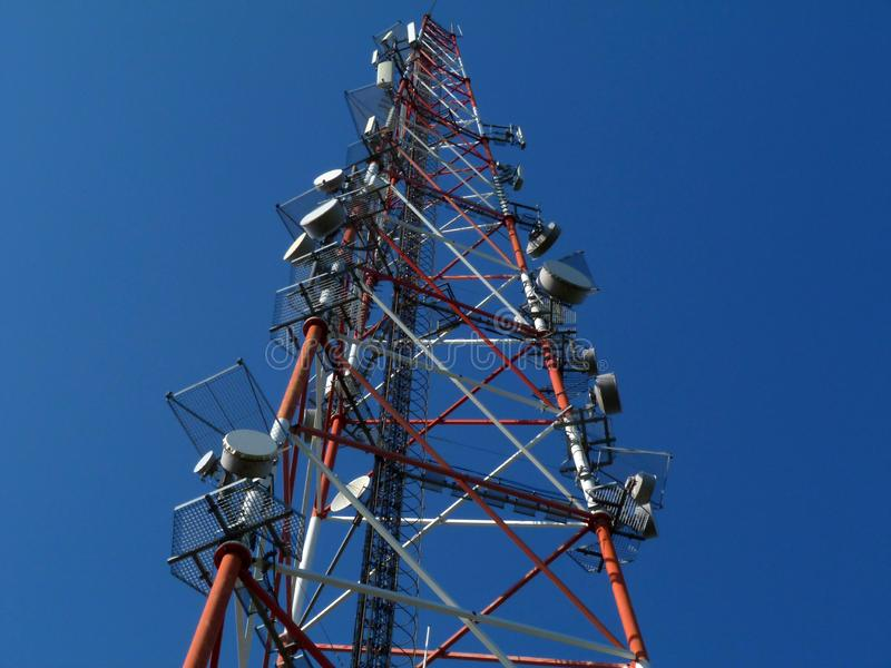 Cell transmitter and receiver tower of red and white steel truss royalty free stock image