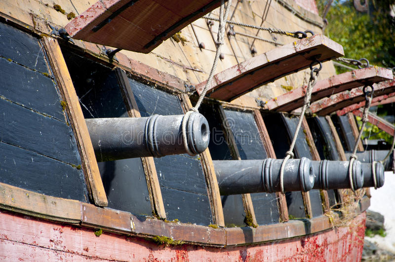 Broadside Cannons. A row of cannons ready for firing from the broadside of a naval ship stock images