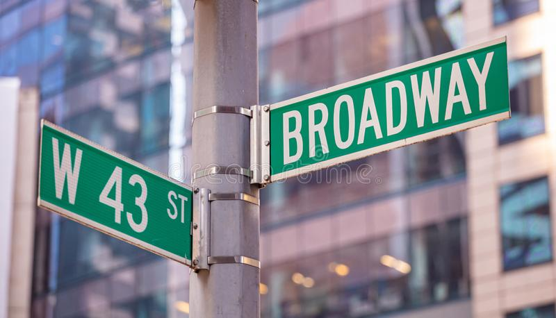 Broadway and W43 corner. Green color street signs, Manhattan New York downtown. Broadway and W43 crossroads street signs. Blur buildings facade background royalty free stock image
