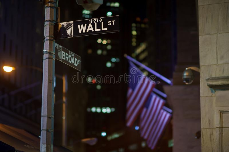 Broadway and Wall Street Signs at the night, Manhattan. Broadway and Wall Street Signs at the night with US flags on background, Manhattan, New York royalty free stock image