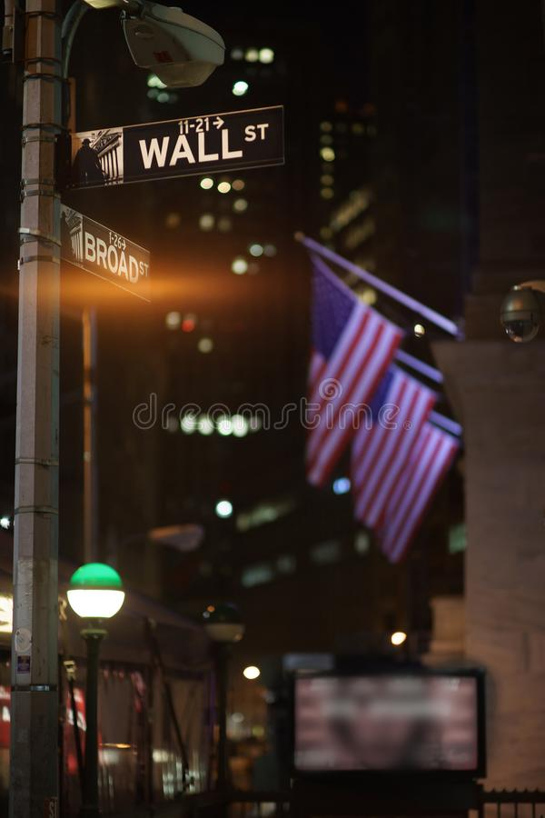 Broadway and Wall Street Signs at the night, Manhattan. Broadway and Wall Street Signs at the night with US flags on background, Manhattan, New York royalty free stock photography