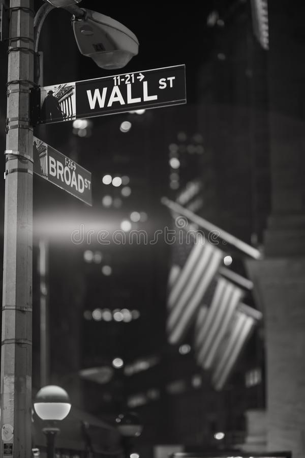 Broadway and Wall Street Signs at the night, Manhattan. Broadway and Wall Street Signs at the night with US flags on background, Manhattan, New York royalty free stock images