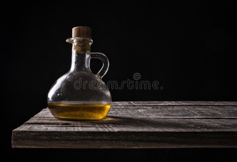 Broc d'huile d'olive sur le vieux bois sur le fond noir images stock