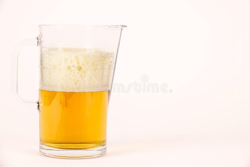 Broc de bière avec la mousse sur le fond blanc photographie stock libre de droits