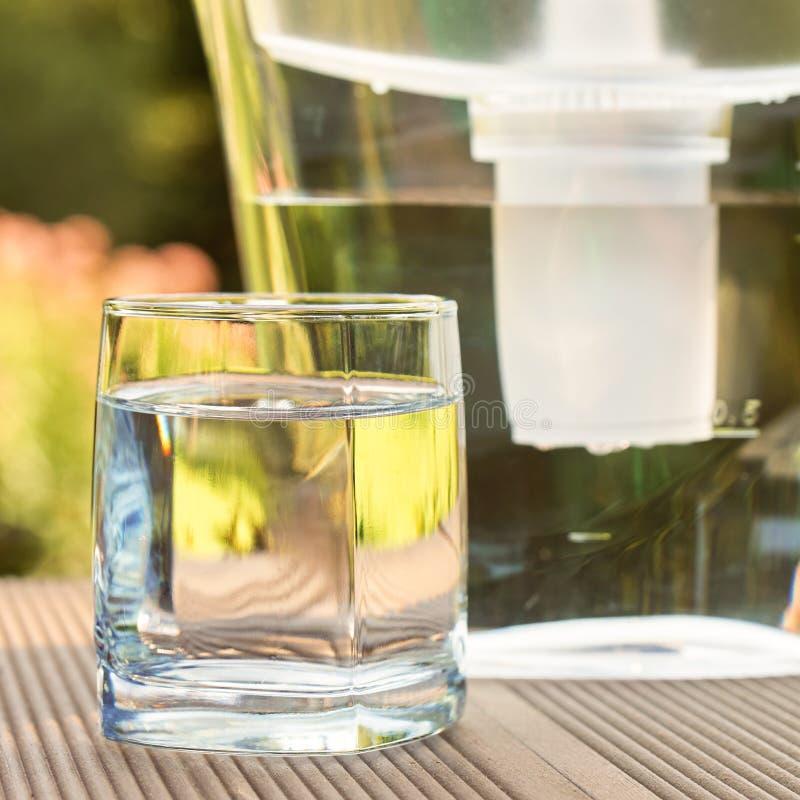 Broc de filtre d'eau et un verre propre d'une fin claire de l'eau sur le fond de jardin d'été photos libres de droits