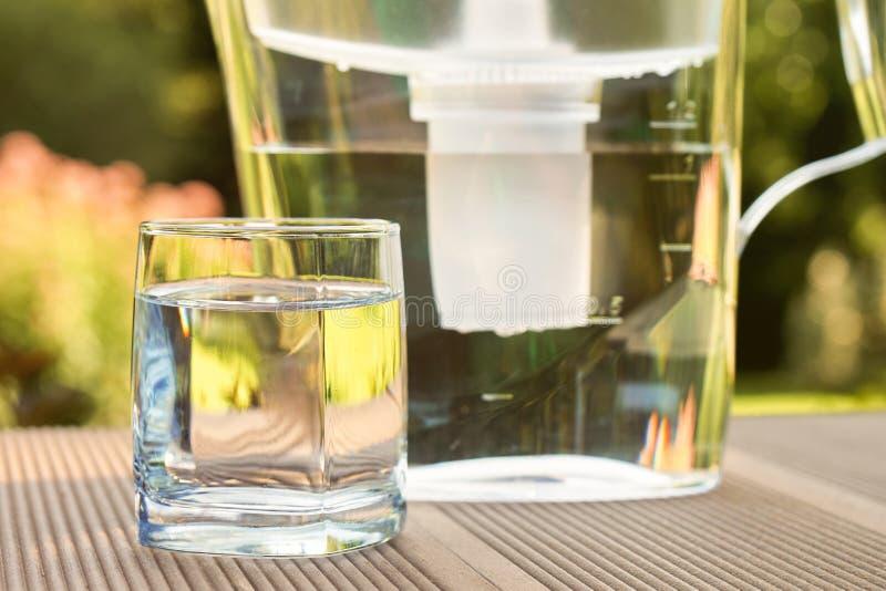 Broc de filtre d'eau et un verre propre d'une fin claire de l'eau sur le fond de jardin d'?t? photographie stock