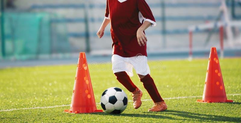 Broca do cone do slalom do futebol Menino na camisa vermelha do jérsei de futebol que corre com a bola entre cones foto de stock royalty free