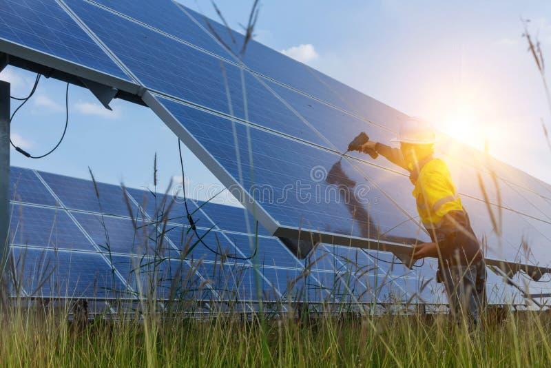 Broca elétrica e do instrumento do técnico do uso da bateria ao sistema elétrico da manutenção no campo do painel solar foto de stock