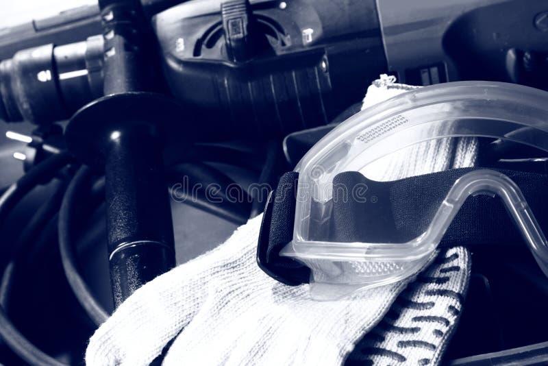 Broca, luvas e óculos de proteção imagens de stock royalty free