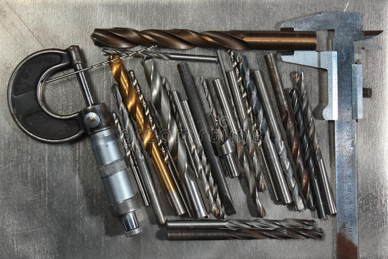 Brocas con micrómetro y calibrador en fondo del metal foto de archivo libre de regalías