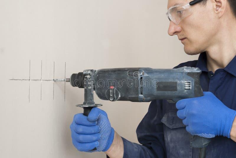Brocas do trabalhador do eletricista uma parede imagem de stock