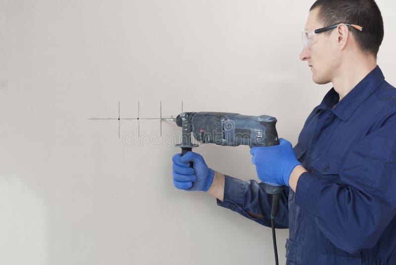 Brocas do trabalhador do eletricista uma parede imagens de stock
