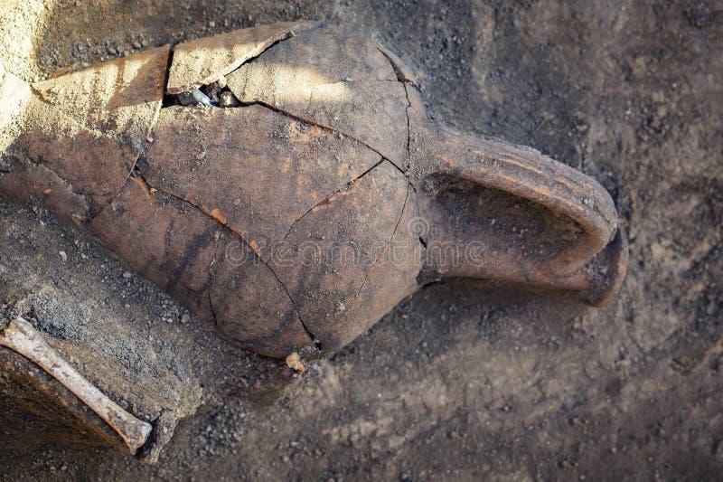 Brocca ceramica antica, anfora ed ossa umane nella sepoltura trovata durante gli scavi archeologici immagine stock