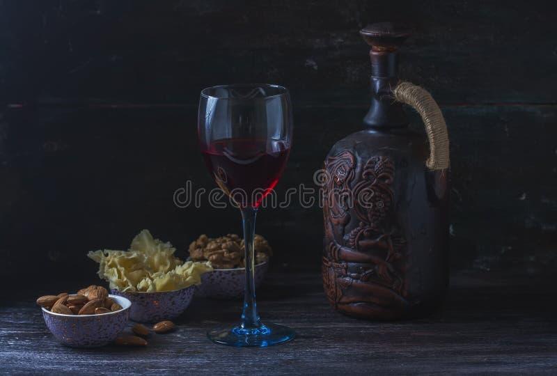 Brocca ceramica per vino, formaggio, dadi su un bordo di legno, fondo fotografie stock libere da diritti