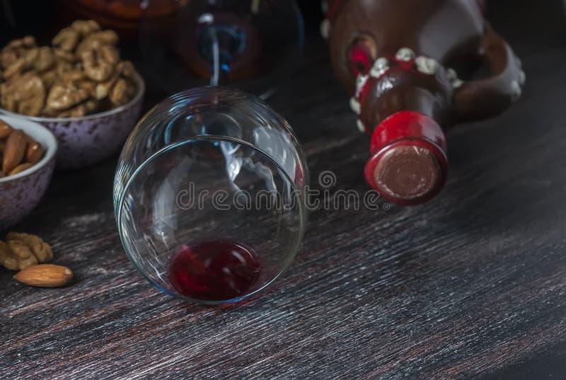 Brocca ceramica per vino, formaggio, dadi su un bordo di legno, fondo immagini stock