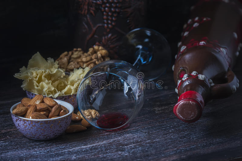 Brocca ceramica per vino, formaggio, dadi su un bordo di legno, fondo fotografia stock libera da diritti