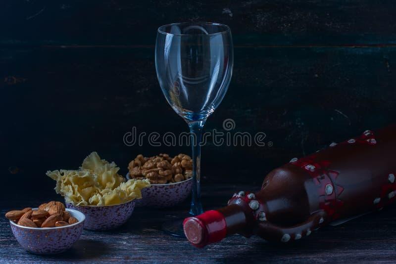 Brocca ceramica per vino, formaggio, dadi su un bordo di legno, fondo immagine stock libera da diritti