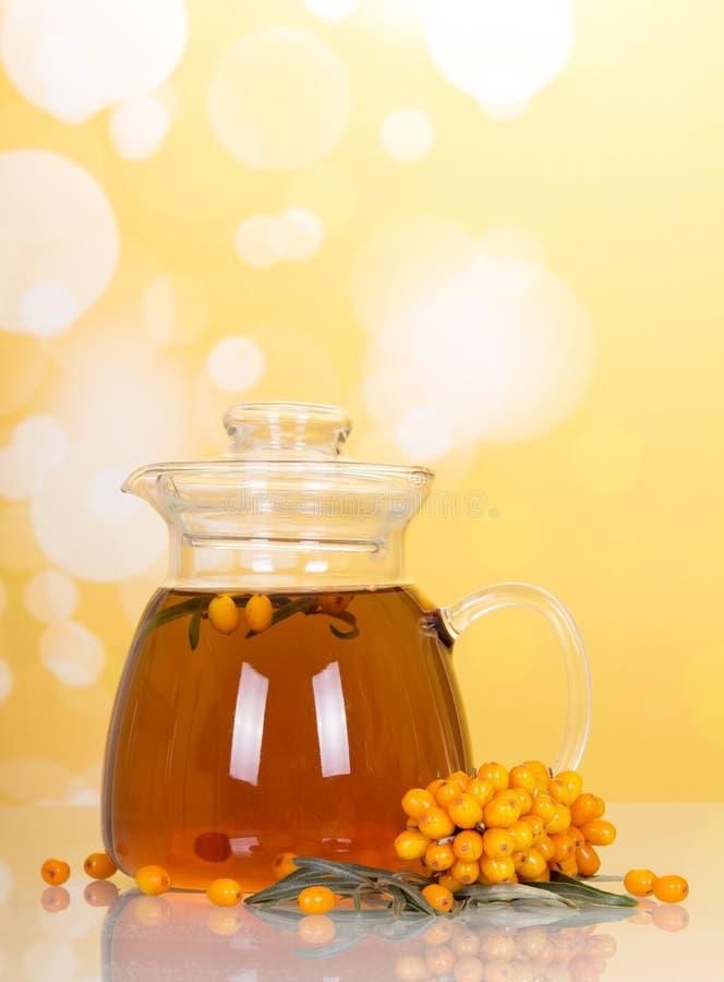 Brocca con la bevanda dell'olivello spinoso su fondo giallo astratto fotografie stock libere da diritti