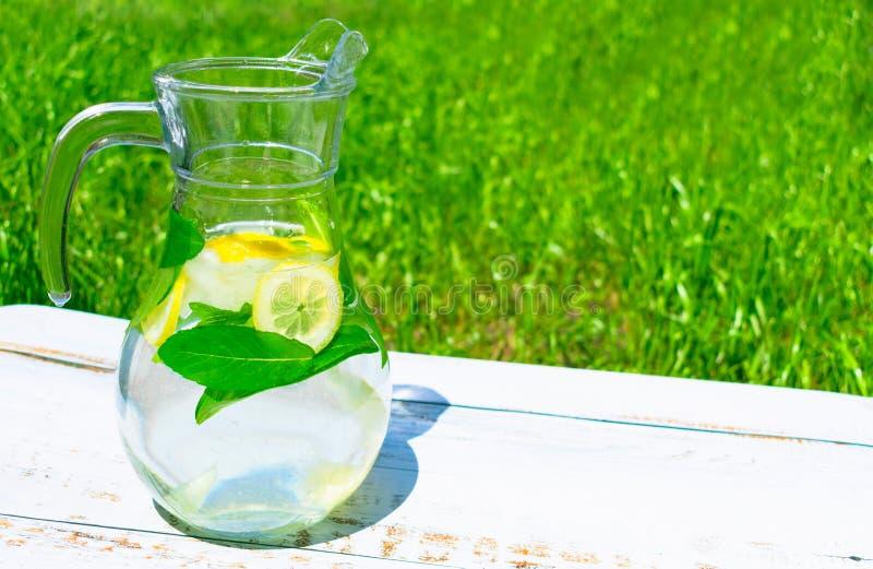 Brocca con limonata dal limone e dalle stuoie con ghiaccio su un fondo di erba verde il concetto delle bibite Primo piano immagine stock libera da diritti