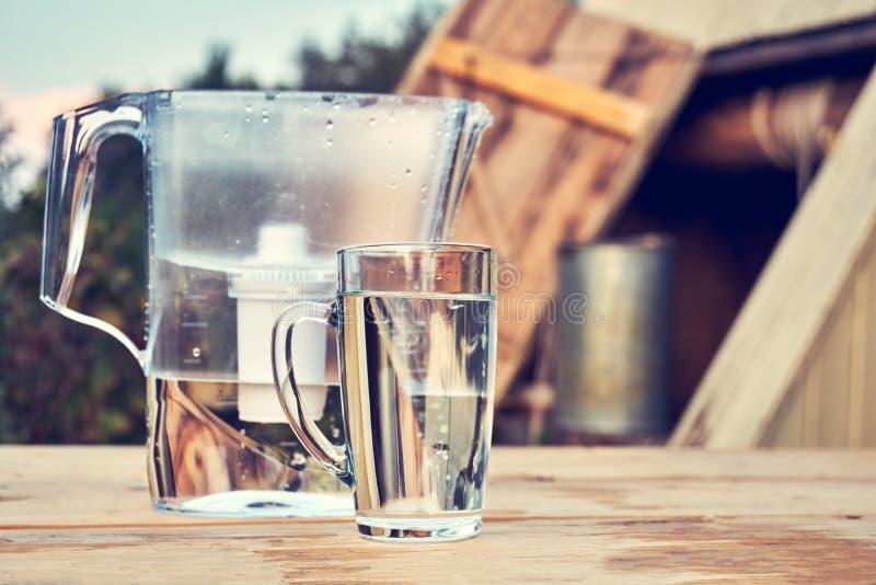 Brocca del filtrante di acqua e una tazza di acqua pulita di vetro trasparente davanti al pozzo di tiraggio di legno all'aperto n fotografie stock