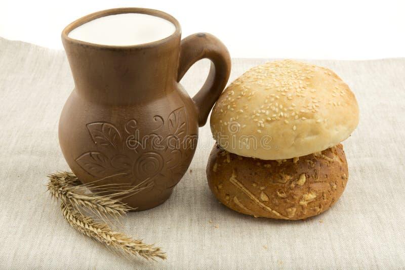 Brocca dell'argilla con latte e pane immagini stock
