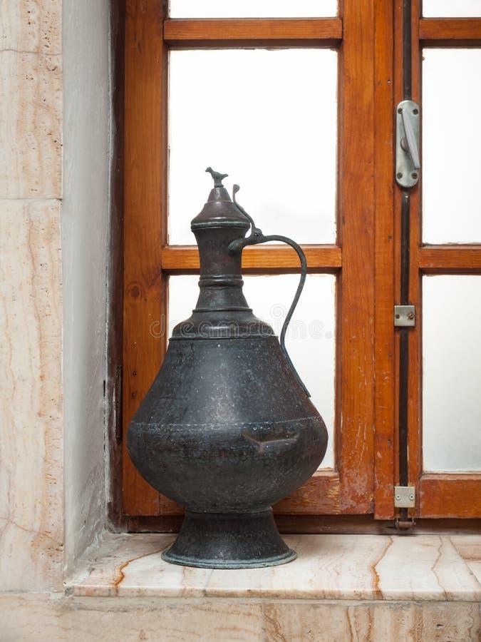 Brocca di acqua antica su un davanzale del bagno immagine stock libera da diritti