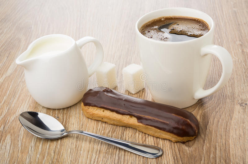 Brocca di latte, eclair con cioccolato, caffè nero in tazza immagini stock libere da diritti