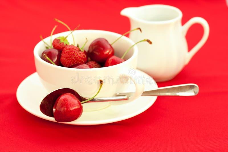 Brocca di latte, tazza, piattino e cucchiaio fotografia stock