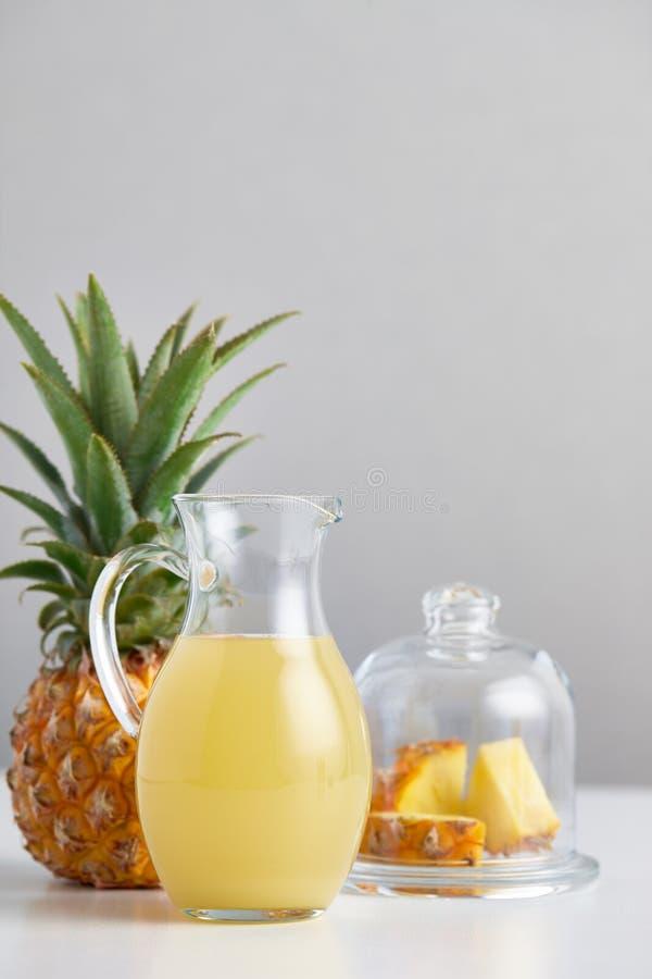 Brocca di vetro con il succo e la frutta di ananas sulla tavola immagini stock