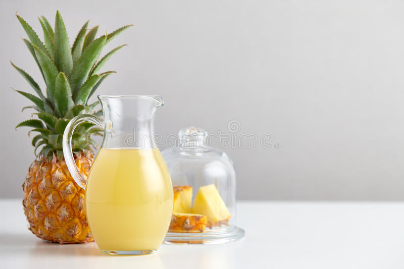 Brocca di vetro con il succo e la frutta di ananas sulla tavola fotografia stock