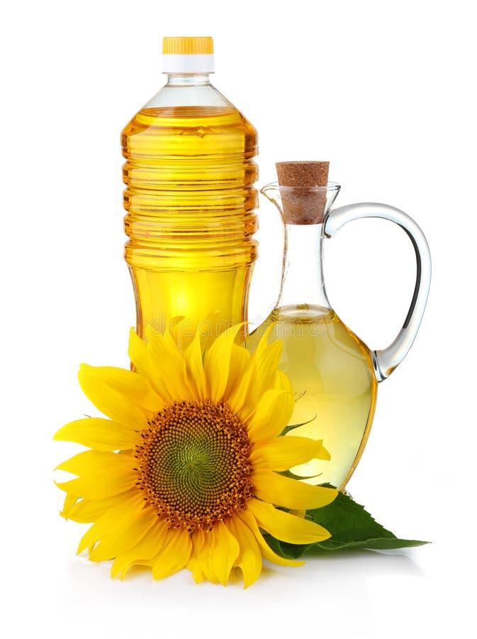 Brocca e bottiglia di olio di girasole con flowe fotografia stock libera da diritti