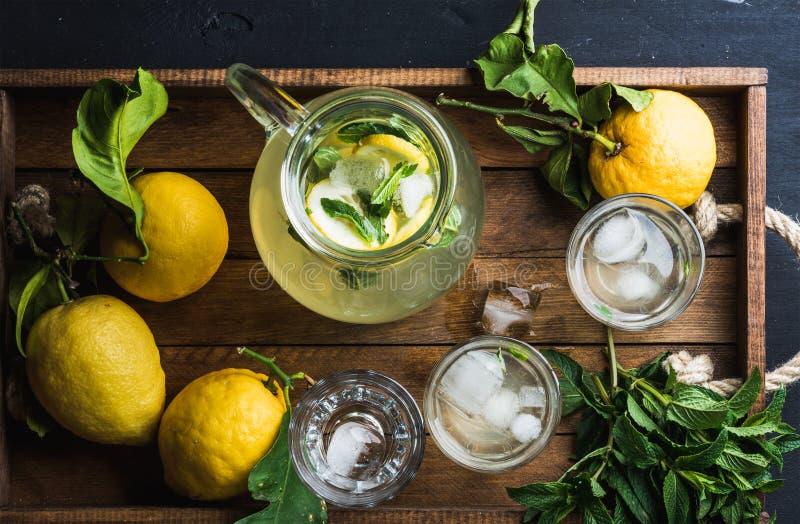 Brocca e vetri con limonata casalinga, cubetti di ghiaccio sul vassoio di legno, vista superiore fotografia stock
